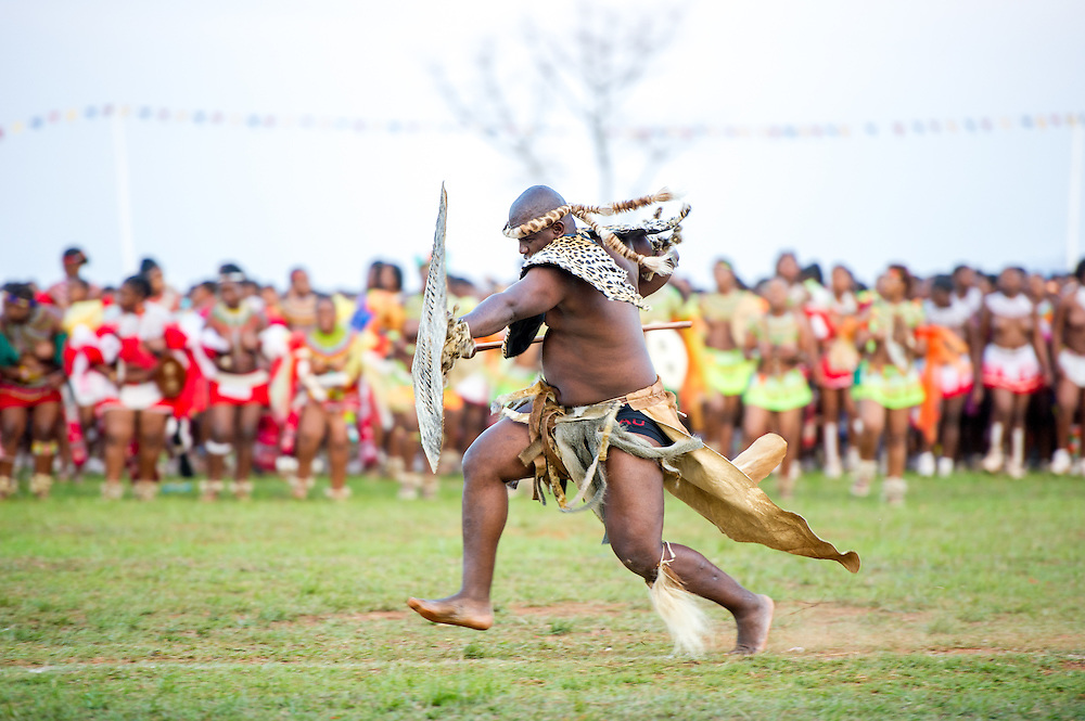 Ludzidzini, Swaziland, Africa - Annual Umhlanga, or reed dance ceremony, in which up to 100,000 young Swazi women gather to celebrate their virginity and honor the queen mother during the 8 day long event.<br /> Warriors take the field