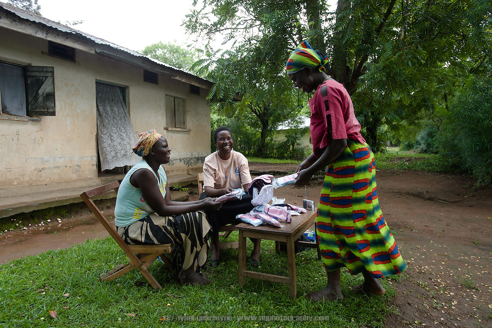"Lovisa Wankya (centre), a teacher and an Afripads dealer, in front of her home near Tororo in Eastern Uganda, explaining how Afripads work to Caroline Adongo (left) and Grace Anyango on 1 August 2014. Having heard of Afripads and ""Madam Wankya"" on the radio, Caroline and Grace were interested in them, but didn't know how to contact Lovisa. They happened to be passing by, and were excited to meet ""Madam Wankya"" and learn about Afripads. They both decided to buy some. (Afripads are reusable fibre sanitary pads that are having a revolutionary impact on menstrual hygiene management, particularly amongst girls and women who cannot afford expesive disposable pads, and who previously had to use rags, cotton wool or toilet paper.)"