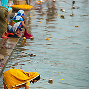 Woman making an offering in Ganges river, Varanasi