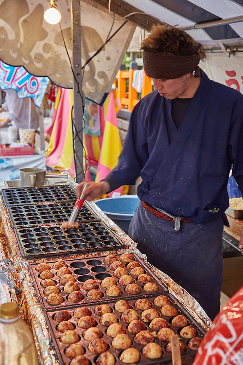 A takoyaki vendor tends to his food. Takoyaki are octopus balls and are a common street food snack throughout Japan, epsecially in the Kansai region where they originate.