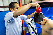 23 DECEMBER 2014 - BANGKOK, THAILAND: A boxer man helps his son cool down between sparring rounds at the Kanisorn gym in Bangkok. The Kanisorn boxing gym is a small gym along the Wong Wian Yai - Samut Sakhon train tracks. Young people from the nearby communities come to the gym to learn Thai boxing. Muay Thai (Muai Thai) is a mixed martial art developed in Thailand. Muay Thai became widespread internationally in the twentieth century, when Thai boxers defeated other well known boxers. A professional league is governed by the World Muay Thai Council. Muay Thai is frequently seen as a way out of poverty for young Thais. Muay Thai professionals and champions are often celebrities in Thailand.     PHOTO BY JACK KURTZ