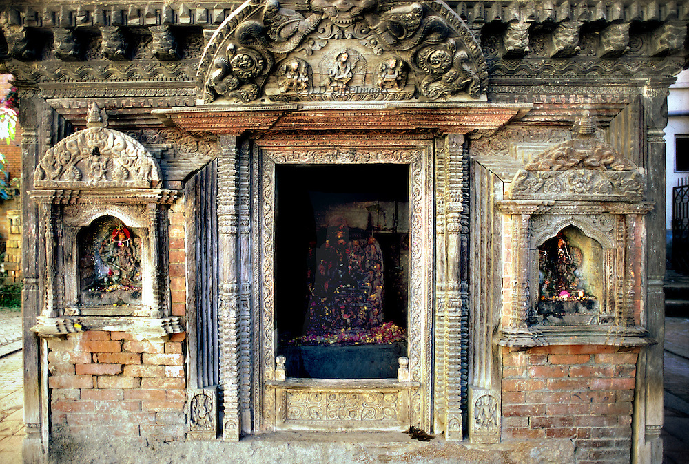 Close up view of the facade of a small Hindu shrine in a Patan town square.  Statue of the deity dimly visible inside, covered with marigold petals for the Dasain festival.  Niche shrine in the wall on each side of the entrance.  Carved stone imitating Newari wood style, with brick infill.