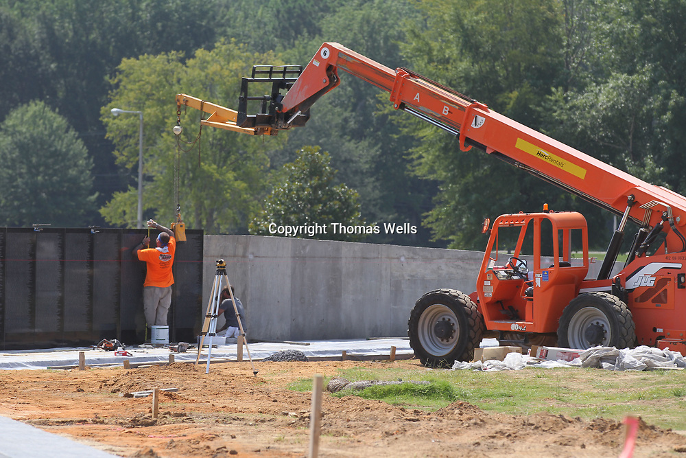 Phillip Taylor and Roger Cole use a lift to hold a marble section wall in place so they can secure it in place as they begin to install the marble panels to complete the Vietnam Memorial Wall at Veterans Park in Tupelo. The wall is one of three premenant replcia's that have built outside of the original in Washington D.C.