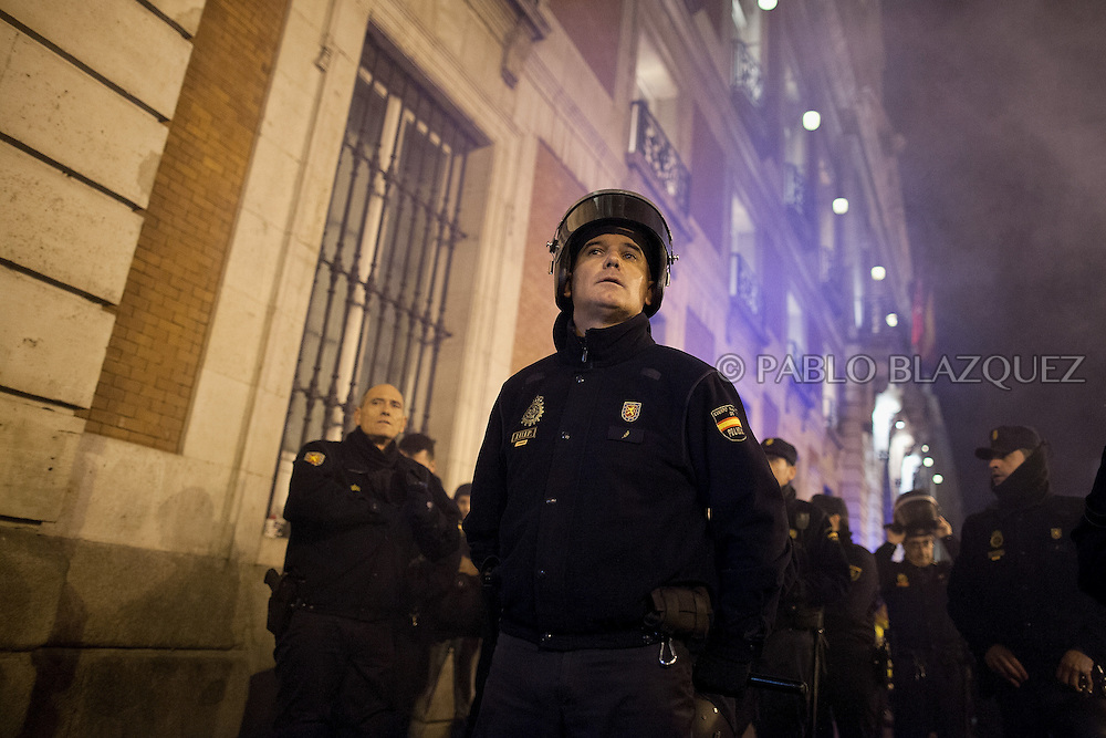 Riot policemen stand outside the Madrid Regional Government headquarters during a 'Surrounding the Congress' protest at Puerta del Sol Square on December 14, 2013 in Madrid, Spain. Social movements groups called a 'Rodea el Congreso' 'Surrounding the Parliament' protest in reaction to the financial and social cuts, but also a new law the Spanish government is working that aims to set heavy fines. Around 1,500 policemen were on duty to protect the congress. The bill will set up fines of up to 30,000 euros for offenses related to social movements protests, insulting the state or offending or filming the authorities. After the demonstration some protesters clashed with riot policemen