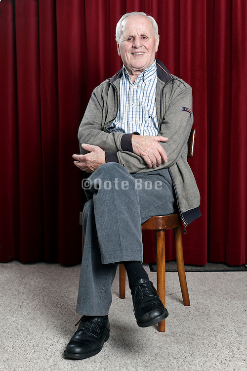portrait of a happy smiling 89 year old man sitting on a chair