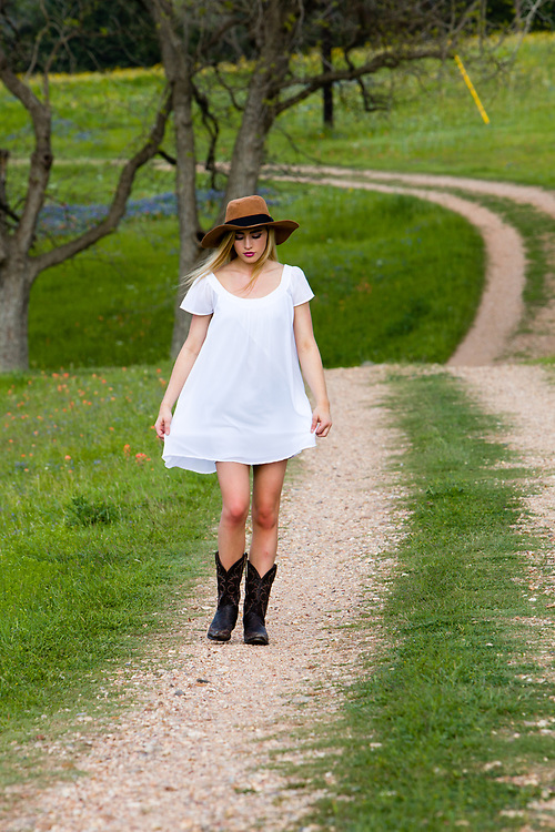 Houston model Savannah O'Hara in coungry hat and boots on dirt road.