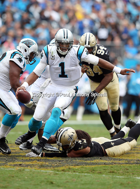 Carolina Panthers quarterback Cam Newton (1) breaks a tackle attempt as he runs for a third quarter gain of 9 yards during the 2015 NFL week 3 regular season football game against the New Orleans Saints on Sunday, Sept. 27, 2015 in Charlotte, N.C. The Panthers won the game 27-22. (©Paul Anthony Spinelli)