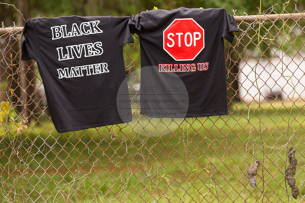 Black Lives Matter tee-shirts hung on the fence near the spot where unarmed black motorist Walter Scott was gunned down by police following a traffic stop April 10, 2015 in Charleston, South Carolina. Scott was shot multiple times in the back and died on the scene after running from police.