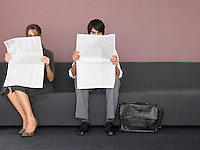 Businesswoman and Businessman Reading Newspapers