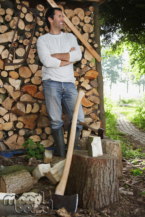 Man standing by axe at timber shed