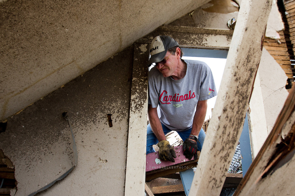 May 25, 2011- Keith Harden crawls through a doorway of his house in Joplin, Missouri after a Tornado came through the town on Sunday, May 22, 2011. Credit: David Welker / TurfImages.com