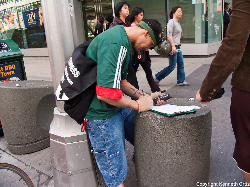 A Bike Messenger is filling out his delivery paperwork on Broadway in Midtown Manhattan.