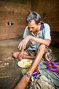 "29 OCTOBER 2012 - MAYO, PATTANI, THAILAND:  SUKRIA eats in his room at the Bukit Kong home in Mayo, Pattani. After saying his name is Sukria he added, ""I have so many names I don't remember who I am anymore."" He is kept shackled in his room at the home. The home opened 27 years ago as a ponoh school, or traditional Islamic school, in the Mayo district of Pattani. Shortly after it opened, people asked the headmaster to look after individuals with mental illness. The headmaster took them in and soon the school was a home for the mentally ill. Thailand has limited mental health facilities and most are in Bangkok, more than 1,100 kilometers (650 miles) away. The founder died suddenly in 2006 and now his widow, Nuriah Jeteh, struggles to keep the home open. Facilities are crude by western standards but the people who live here have nowhere else to go. Some were brought here by family, others dropped off by the military or police. The home relies on donations and gets no official government support, although soldiers occasionally drop off food. Now there are only six patients, three of whom are kept chained in their rooms.  Jeteh says she relies on traditional Muslim prayers, holy water and herbal medicines to treat the residents. Western style drugs are not available and they don't have a medic on staff.    PHOTO BY JACK KURTZ"