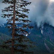 The sun and clouds exchange colors and drama at sunset in Mount Rainier National Park, Washington.