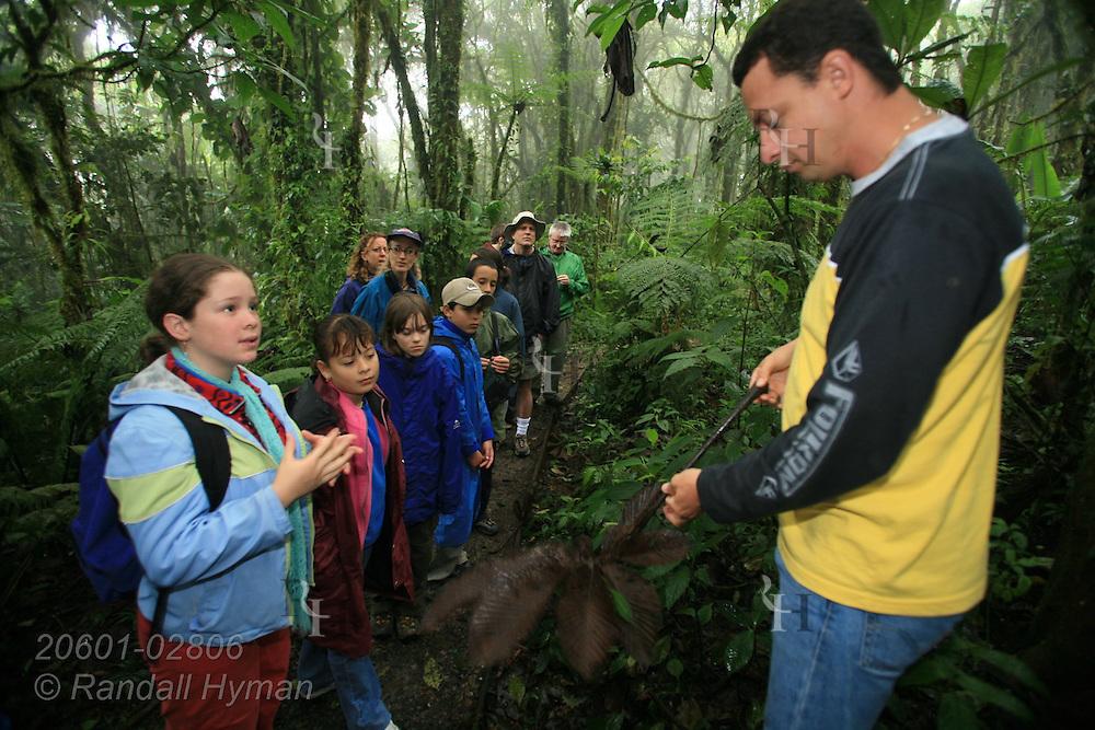 Ecoteach guide Alex Alvarez Rojas leads nature hike in rainforest while Cloud Forest School sixth-grader Jocelyn Mena Mora asks question; Santa Elena National Park, Costa Rica.