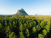 Aerial photograph of Mt Coonowrin (left) & Mt Tibrogargan & surrounding native and farmed pine tree forest, Glasshouse Mountains, Queensland, Australia