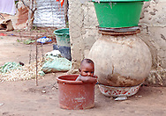 A toddler plays in a plastic bucket in one of the small breeze block hut settlements growing up around the fishing town of M'bour, Senegal.  M'bour is currently the 5th largest, and one of the fastest growing town in Senegal.  With unemployment high, men arrive to find work in the, largely unregulated fishing industry.  Around the main town small clusters of huts and shacks spring up to house this burgeoning population.