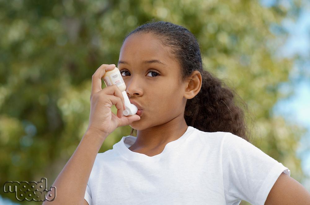 Girl (7-9) using inhaler, outdoors