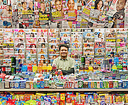 Magazine stand with smiling owner sells magazines and candy in the New York City subway.