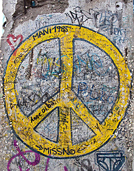 Detail of peace symbol painted on remaining section of Berlin Wall