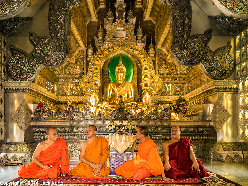 "03 APRIL 2016 - CHIANG MAI, THAILAND: Buddhist monks look at and comment about the interior of the ordination hall of Wat Sri Suphan. Wat Sri Suphan is also known as the ""Silver Temple"" because of its silver ubosot, or ordination hall. The temple is more than 500 years old but the silver ordination hall was recently remodeled. The ordination hall is covered in silver and the interior is completely done in silver and gold. It's traditionally served as the main temple for the silversmiths of Chiang Mai, whose community is around the temple.     PHOTO BY JACK KURTZ"