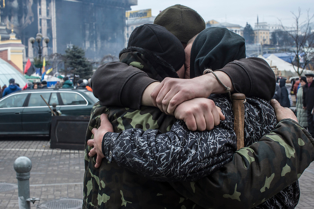 KIEV, UKRAINE - FEBRUARY 23: A group of anti-government protesters share a hug on Independence Square on February 23, 2014 in Kiev, Ukraine. After a chaotic and violent week, Viktor Yanukovych has been ousted as President as the Ukrainian parliament moves forward with scheduling new elections and establishing a caretaker government. (Photo by Brendan Hoffman/Getty Images) *** Local Caption ***