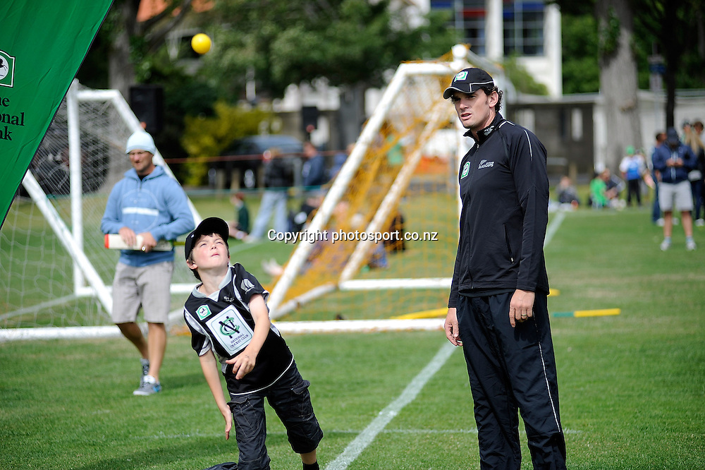 Kyle Millis looks on as cricket fan bowls the ball, at the National Bank's Cricket Super Camp , University oval, Dunedin, New Zealand. Thursday 2 February 2012 . Photo: Richard Hood photosport.co.nz