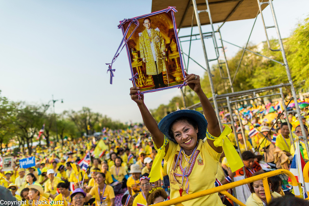 05 MAY 2104 - BANGKOK, THAILAND: A supporter of the Thai monarchy holds a photo of Bhumibol Adulyadej, the King of Thailand, over her head during a Coronation Day rally in Bangkok. Thousands of Thais packed the area around Sanam Luang and the Grand Palace Monday evening for a special ceremony to mark Coronation Day, which honored the 64th anniversary of the coronation of Bhumibol Adulyadej, the King of Thailand. Many of the people also support the anti-government movement led by Suthep Thaugsuban. Most of the anti-government protesters are conservative supporters of the monarchy.    PHOTO BY JACK KURTZ