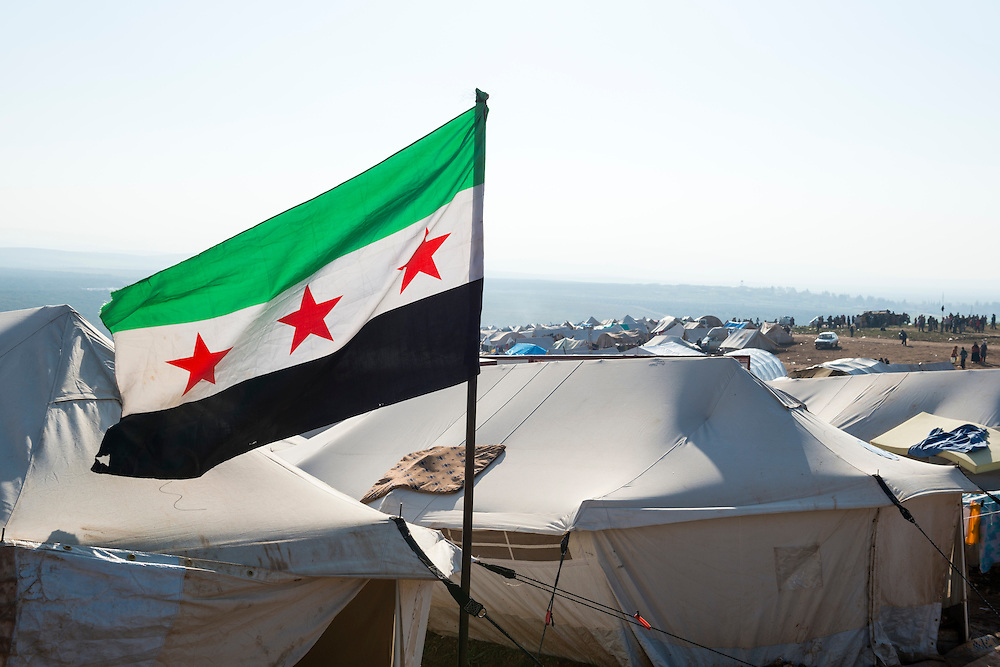 A Free Syrian flag flies outside tents at the camp for displaced persons in Atmeh, Syria