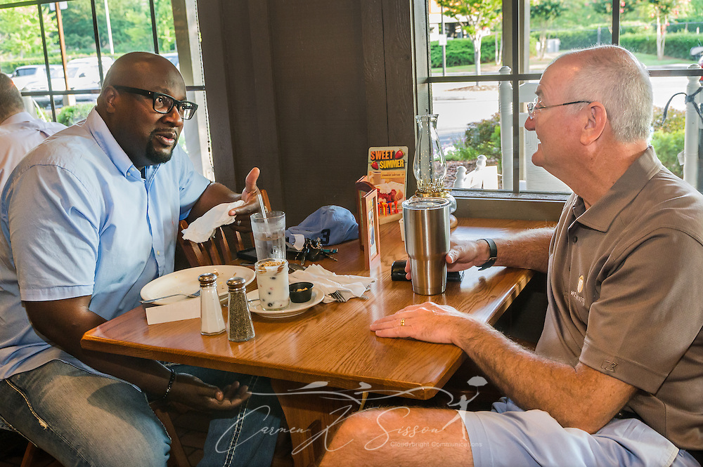 Alton Hardy, pastor of Urban Hope Community Church in Fairfield, and Bob Flayhart, pastor of Oak Mountain Presbyterian Church in Birmingham, talk during breakfast at Cracker Barrel, July 17, 2015, in Birmingham, Ala. Hardy and Flayhart began having weekly breakfasts together more than two years ago — a move they say has been instrumental in forming the trusting relationship needed as their congregations work together to heal race relations in Birmingham. (Photo by Carmen K. Sisson)
