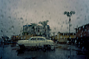Vintage car in parking lot with raindrops on window