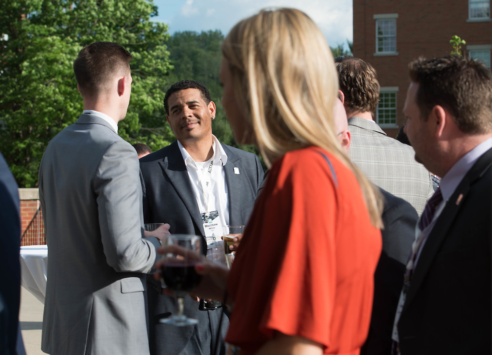 Matthew White, a professional master of sport adminstration student, laughs with Andy Dolich at the Charles R. Higgins Distinguished Alumnus Award Banquet outside of Nelson Commons. © Ohio University/ Photo by Kaitlin Owens