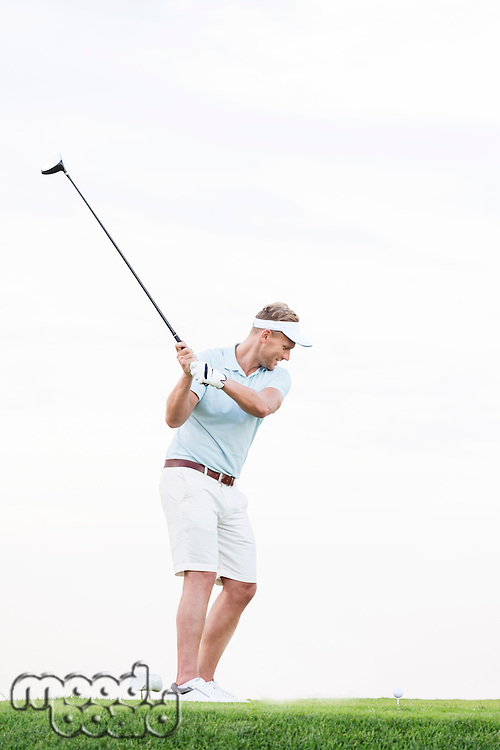 Full-length of mid-adult man swinging golf club against clear sky