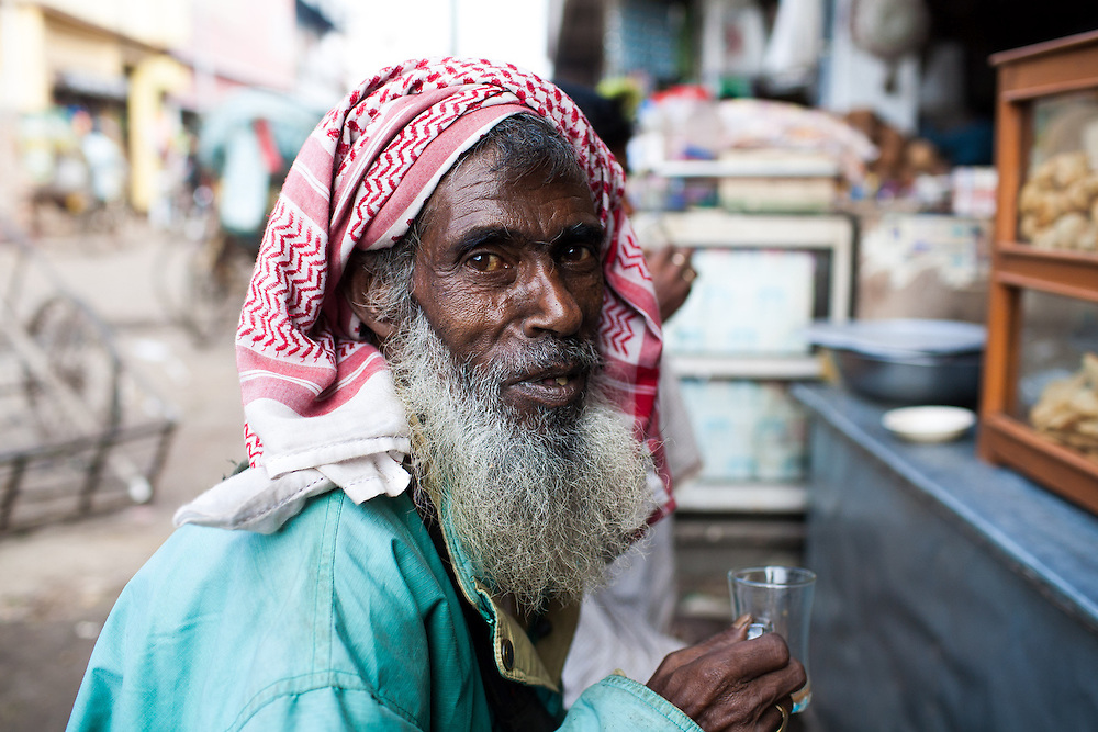 A Bangladeshi muslim man drinks a small cup of tea in the municipal market in Srimongol in the tea growing region of north east Bangladesh