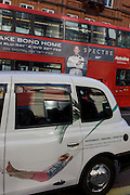 A man in a hammock advertises an investment and pensions savings company on a London taxi cab with an ad for the latest James Bond film Spectre, on DVD soon.