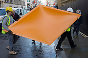 Workmen carry a diamond-shaped item that will form part of the exterior facia to Louis Vuitton in Bond Street, during the shop's interior renovation, on 3rd December 2018, in London, UK
