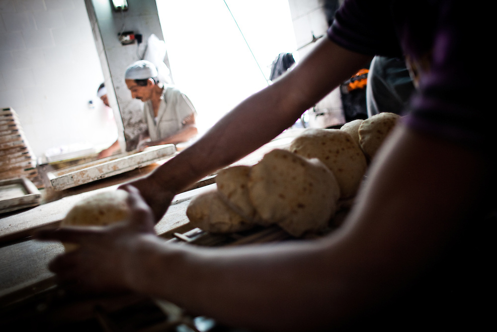 A baker places bread on a wooden rack to be  sold.