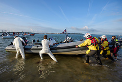 © Licensed to London News Pictures. 24/08/2017. Solent, UK. Members of the RNLI give two crickets help unbeaching their boat after the match. Teams take part in the Brambles Bank Cricket Match in the middle of The Solent strait on August 24, 2017. The annual cricket match between the Royal Southern Yacht Club and The Island Sailing Club, takes place on a sandbank which appears for 30 minutes at lowest tide. The game lasts until the tide returns. Photo credit: Ben Cawthra/LNP