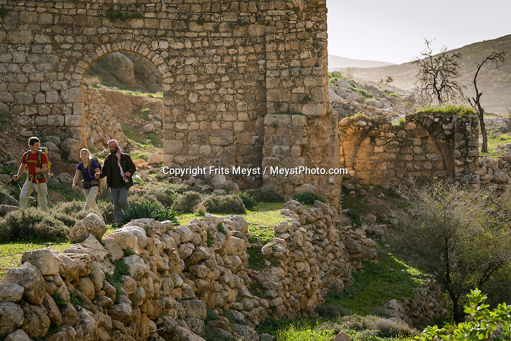 Palestine, March 2015. Hikers in front of an Ottoman era aquaduct at Ein Samiya on the trail from Duma to Kafr Malek. The Abraham Path is a long-distance walking trail across the Middle East which connects the sites visited by the patriarch Abraham. The trail passes through sites of Abrahamic history, varied landscapes, and a myriad of communities of different faiths and cultures, which reflect the rich diversity of the Middle East. Photo by Frits Meyst / MeystPhoto.com for AbrahamPath.org