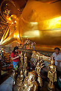 Wat Po, Temple of the Reclining Buddha. Worshippers applying gold leafs to Buddha and monk statues.