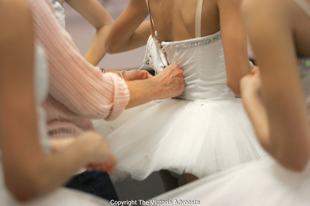 PHOTO BY JODI MILLER FOLDER 031306.Debbe Busby makes some adjustments to a tutu during a rehearsal Tuesday afternoon.