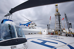 Helicopters land on helideck of an offshore oil drilling rig.