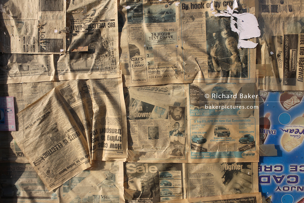Faded newspaper sheets are stuck to a closed newsagent's window in Dulwich, South London UK