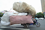 SHAOXING, CHINA - AUGUST 28: (CHINA OUT) <br /> <br /> A man rides a motor tricycle carrying bags of plastic foams on a road on August 28, 2013 in Shaoxing, Zhejiang Province of China. <br /> ©Exclusivepix