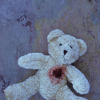 Pale beige teddy bear lying face up on purple and orange rough slate with possible gunshot wound in heart
