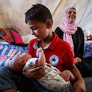 Yahya, 11, a refugee from Idlib, Syria, holds his baby brother, Ahmed, 25 days, who was born in the camp. Their mother, Hanan, 33, is in the background. Ritsona Refugee Camp, Ritsona, Greece. July 2016.