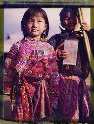Polaroid 79 portrait of a little girl wearing colorful traditional handmade clothes with her grandmother standing behind holding a Polaroid, Ha Giang, Northern Vietnam, Southeast Asia