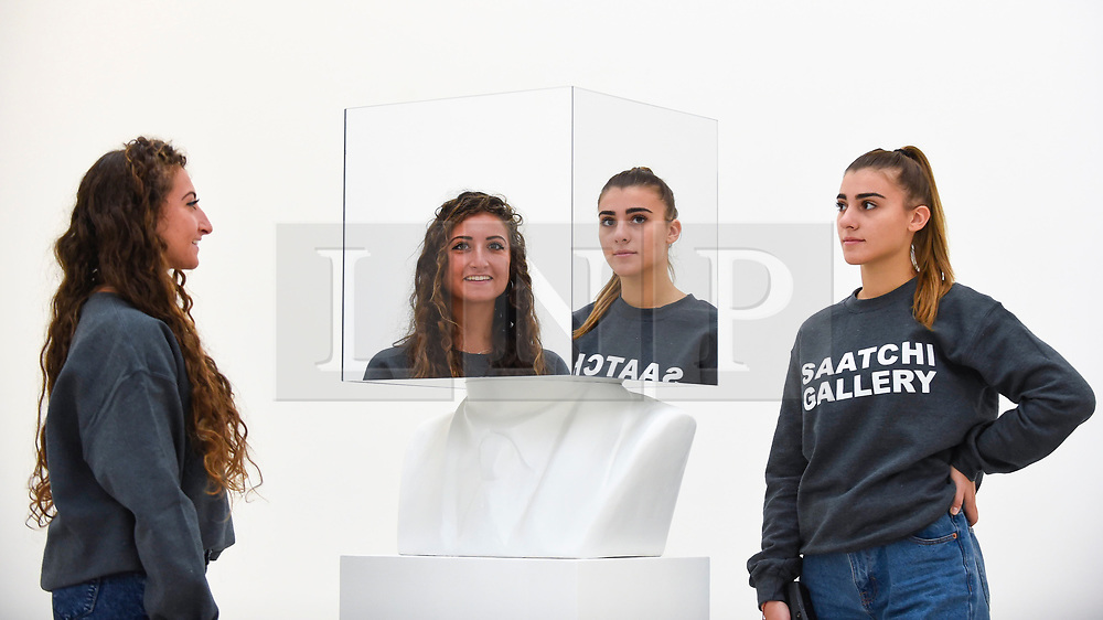 "© Licensed to London News Pictures. 27/09/2018. LONDON, UK. Staff members pose with ""The artist should never contemplate making a work of art that is about something; a successful work of art can only ever be about nothing. The artist's complete negation of intent thus creating a reflective surface into which the critic, curator or collector can gaze and see only himself. Sol LeWitt, Paragraphs on Conceptual Art, 1967"", 2012, a mirror work by Scott King.   Preview of ""Black Mirror"", a major new exhibition featuring the work of 26 contemporary artists, at the Saatchi Gallery.  The show explores art's role in social satire and how political uncertainty has influenced art of recent years and runs 28 September to 13 January 2019.   Photo credit: Stephen Chung/LNP"