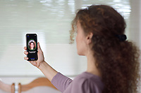 Young woman with iPhone X setting up Face ID, biometric authentication, by scanning her face with a new depth sensing camera