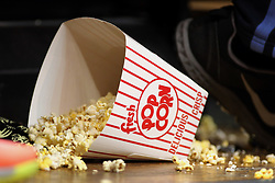 04 January 2015:  a spilled container of popcorn is distributed across the floor with some remaining in the container.